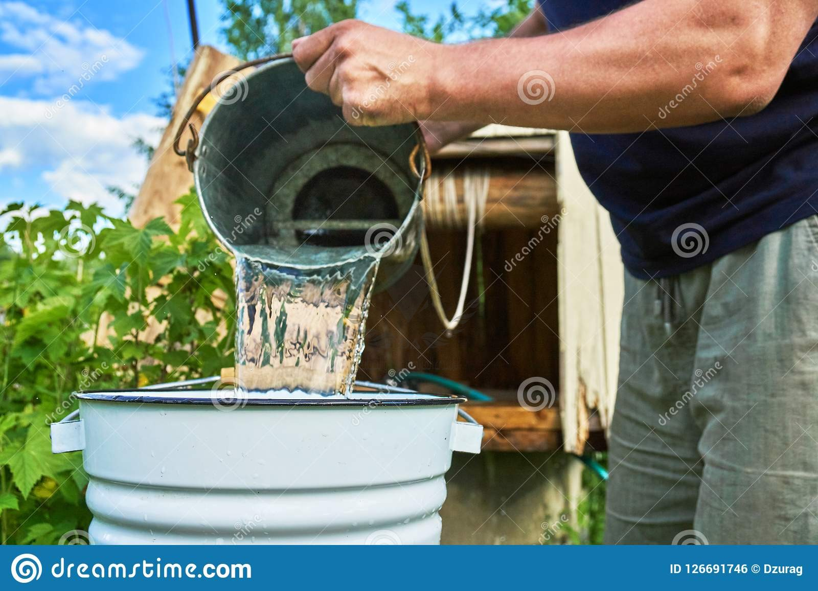 man-pouring-water-just-taken-up-well-enameled-bucket-man-pouring-water-just-taken-up-well-enam...jpg